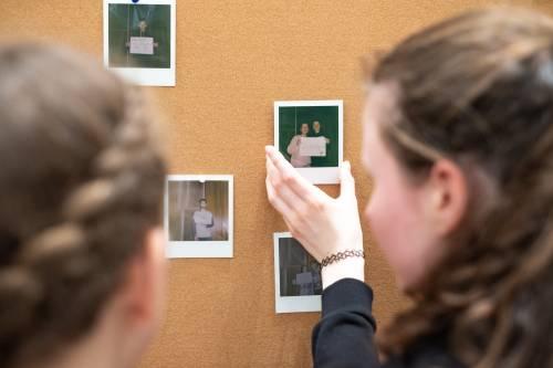 Blick über die Schulter einer jungen Frau. Sie heftet ein Polaroid Bild an eine Korkwand.