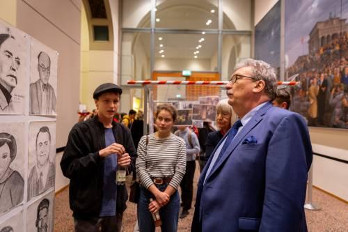 Präsident Wieland betrachtet Porträtzeichnungen in einer Ausstellung. Neben ihm stehen weitere Menschen.