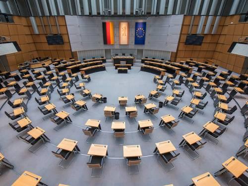 Blick von der Besuchertribüne in den Plenarsaal mit den halbrund angeordneten Sitzen und Tischen.