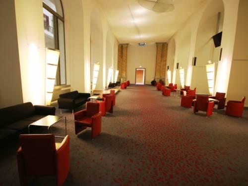 Blick in die sogenannte Wandelhalle vor dem Plenarsaal. Es stehen rote Sessel in kleinen Gruppen zusammen.