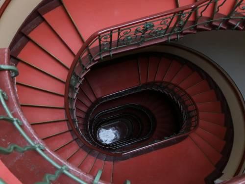 Historisches rundes Treppenhaus mit roten Fußboden, Blick von oben.