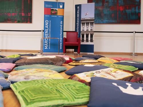 Bunte Sitzkissen auf der Erde im Festsaal, Plakat der Berliner Märchentage.