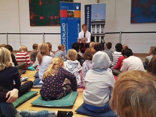 Kinder sitzen auf Kissen auf dem Fußboden. Ein Mann in Hemd und Krawatte liest aus einem Märchenbuch vor.
