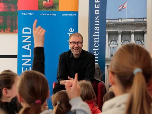Daniel Buchholz sitzt lachend vor einer Kindergruppe.