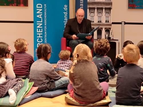 Ein Mann im schwarzen Sakko liest ein Märchen Kindern vor, die vor ihm auf dem Boden sitzen.