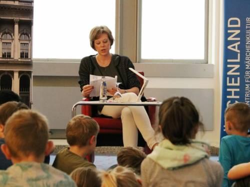 """Vizepräsidentin Cornelia Seibeld liest den kleinen Gästen aus der Geschichte über die aberwitzigen Tauschgeschäfte des """"Hans im Glück"""" vor."""