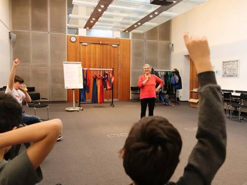 Eine Frau steht in der Mitte eines Raumes und spricht zu Kindern. Einige Kinder melden sich.