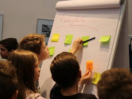 """Kinder verteilen farbige Notizzettel auf einem Flipchart mit der Aufschrift """"Fähigkeiten""""."""