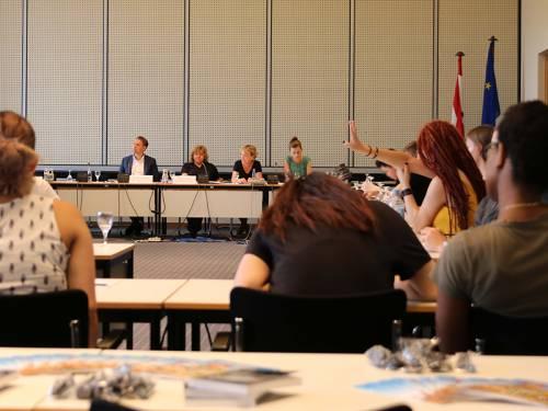 Schulklasse während eines Rollenspiels. Es wird eine Auschusssitzung nachgestellt. Eine Schülerin hebt die Hand.