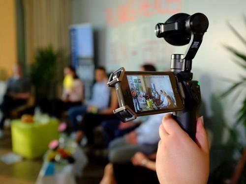 Fokus auf ein Handy am Stativ, welches von einer Hand gehalten wird. Das Handy zeichnet eine Video von einer Gesprächsrunde auf.