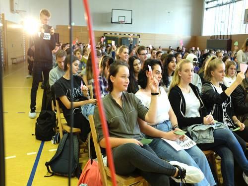 Schülerinnen und Schüler sitzen in einer Turnhalte und halten Stimmzettel in die Höhe.