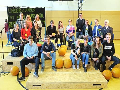 Gruppenfoto von Schülerinnen und Schülern sowie Abgeordneten in einer Turnhalle.