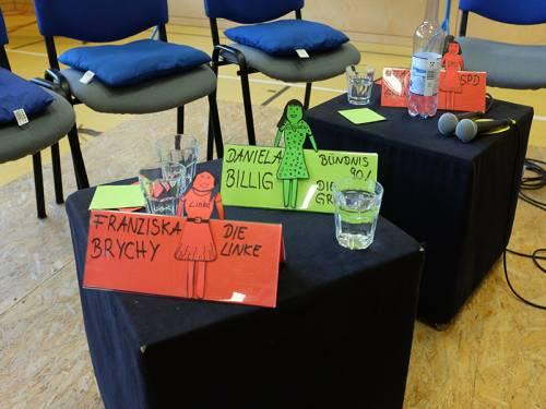 Auf schwarzen Würfeln stehen Namensschilder von Abgeordneten. Daneben stehen Wassergläser und Mikrofone.