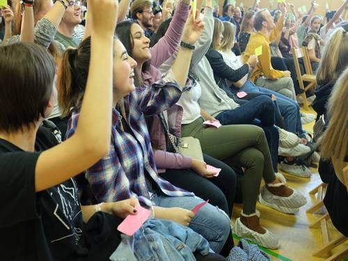 Schülerinnen und Schüler sitzen in der Aula und halten Stimmzettel in die Höhe. Die meisten lachen dabei.