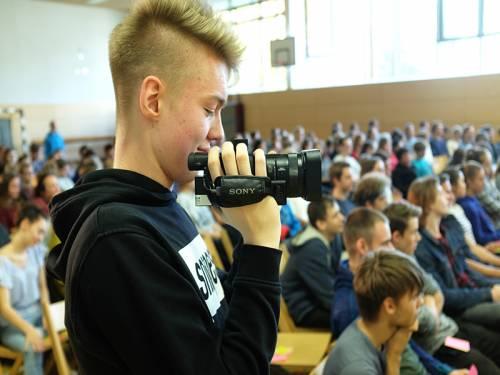 Ein Schüler filmt in der Turnhalle eine Veranstaltung. In der Turnhalle sitzen Schülerinnen und Schüler.