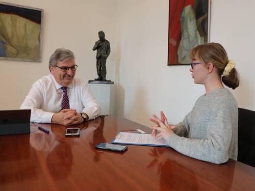 Eine Schülerin sitzt mit Ralf Wieland an einem Besprechungstisch und stellt ihm Fragen.