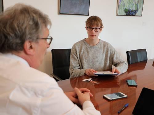 Blick über die Schulter von Ralf Wieland auf eine junge Schülerin, die mit ihm am Besprechungstisch sitzt.