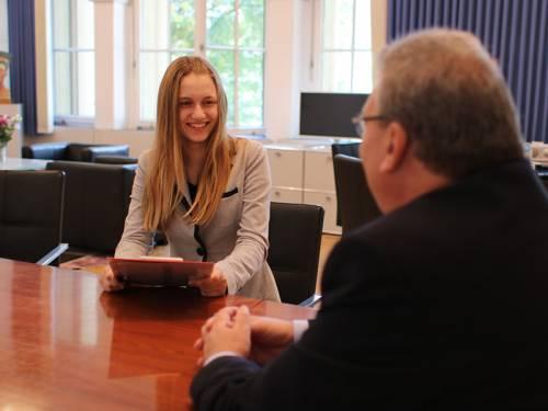 Ein junges Mädchen sitzt mit Ralf Wieland am Besprechungstisch und lacht.