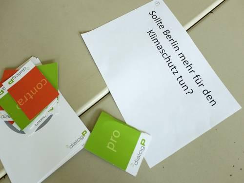 """Ein Zettel mit einer gedruckten Frage """"Sollte Berlin mehr für den Klimaschutz tun?"""" und Pro/Contra Karten auf einem Schultisch."""