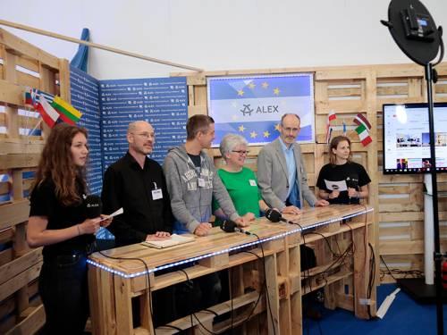 Abgeordnete und junge Menschen im Gespräch in einem mobilen Fernsehstudio aus Holzpaletten.