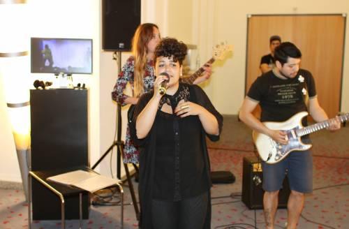 Eine Band spielt Musik. Im Vordergrund eine Sängerin, im Hintergrund eine Frau am Bass und ein Mann an einer E-Gitarre.