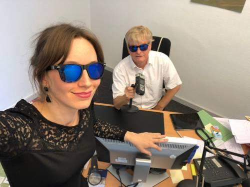 Frau steht im Vordergrund, ist auf einem Monitor gelehnt. Ein Mann sitzt im Hintergrund an einem Stuhl und hat ein Mikrofon in der Hand. Beide tragen eine Sonnenbrille