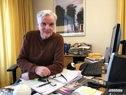Ein älterer Mann sitzt am Schreibtisch seines Büros. Um ihn herum sind ganz viele Papierstapel.