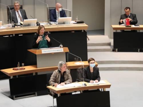 Blick auf das Rednerpult im Abgeordnetenhaus. Eine Frau steht daran und gestikuliert. Im Vordergrund sieht man zwei Frauen vom Stenodienst.