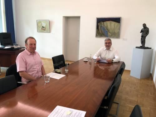 Herr Wieland sitzt mit einem anderen Mann an einem langen Besprechungstisch in seinem Büro.