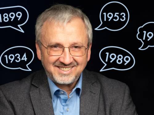Portrait von Herr Rögner-Francke. Um ihn herum sind grafische Sprechblasen mit Jahreszahlen.