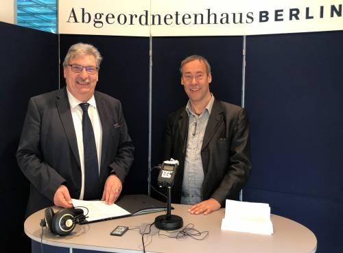 Herr Wieland steht in einem mobilen Radiostudio mit einem anderen Mann. Beide lachen in die Kamera.