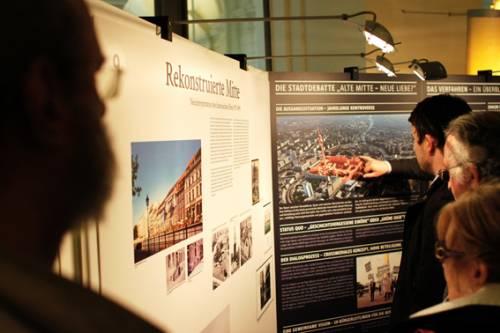 Ausstellungsbesucher betrachten Fotos von der Berliner Stadtmitte.