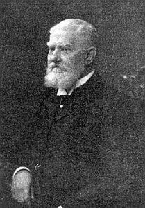 Schwarz Weiß Aufnahme eines älteren Mannes mit weißen Haarenund weißen Bart und einem dunklen Anzug.