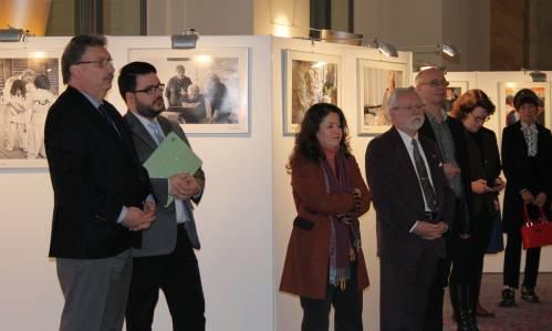 Besucher und Besucherinnen in einer Ausstellung. Sie hören jemanden zu, der außerhalb des Bildes spricht.