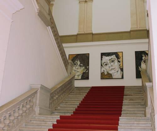 Bild einer Freitreppe mit roten Teppich. Man schaut auf die Zwischenebene, dort hängen drei sehr große gemalte Portraits von Frauen.