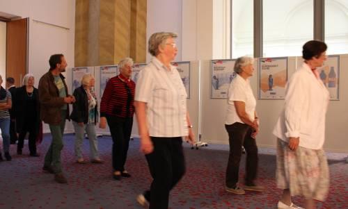 Eine Gruppe ältere Menschen gehen vor Ausstellungstafeln her.
