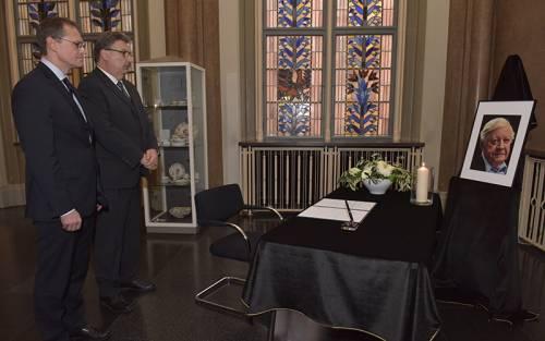 Ralf Wieland und Michael Müller stehen vor einem Tisch mit einem schwarzen Tuch auf dem ein Kondolenzbuch liegt. Eine Kerze brennt und ein Portrai des Verstorbenen wurde aufgestellt.