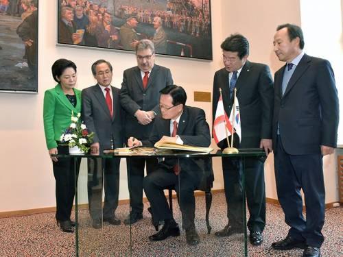 Ralf Wieland mit einer Delegation aus Südkorea. Der südkoreanische Parlamentspräsident unterschreibt in einem Buch.