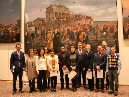 Eine Gruppe von Männern und Frauen zum Gruppenfoto vor einem großen Gemälde, welches den Mauerfall zeigt. Mit ihnen Ralf Wieland.