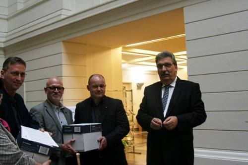 Ralf Wieland steht neben einer kleinen Gruppe Menschen, welche Kartons in den Händen halten.