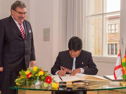 Der Bolivianische Präsident Morales trägt sich in das Goldene Buch der Stadt Berlin ein. Neben ihm steht Parlamentspräsident Wieland.