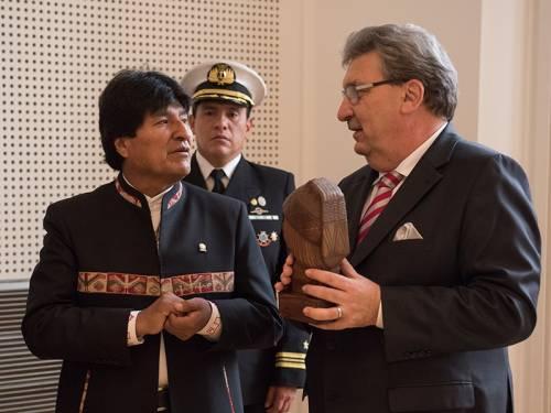 Ralf Wieland hält eine Holzskulptur in den Händen und spricht mit Staatspräsident Morales.
