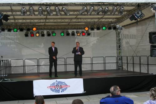 Ralf Wieland steht mit einem anderen Mann auf einer kleinen Bühne vor dem Abgeordnetenhaus.