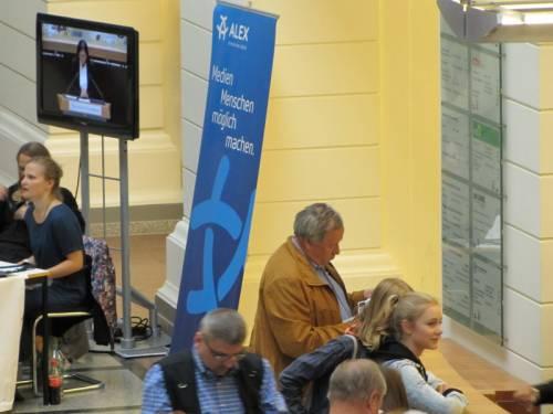 """Menschen stehen in der Eingangshalle am Infotresen. Ein Monitor zeigt, was im Plenarsaal passiert. Auf einem Aufsteller von Alex TV steht: """"Medien Menschen möglich machen."""""""