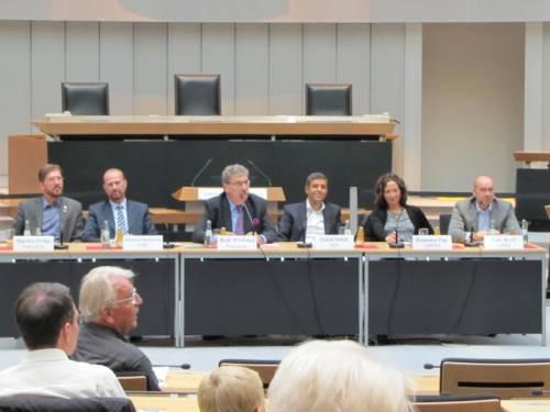 Ralf Wieland sitzt mit anderen Politikern an einem langen Tisch im Plenarsaal. Auf den Sitzen sind andere Zuschauer.