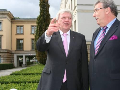 Hr. Wieland steht mit Hr. Bouffier asuf dem Abgeordnetenhaus. Hr. Bouffier hebt die Hand und zeigt auf etwas. Beide tragen schwarze Anzüge und pinke Krawatten.