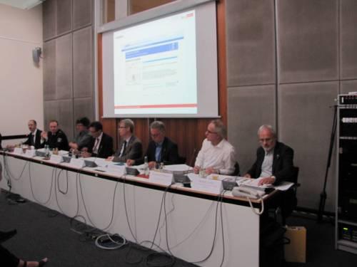 Acht Männer sitzen in einer Art Pressekonferenz an einem langen Tisch mit Mikrofonen. Hinter ihnen wird ein Bild auf dem Beamer projiziert.