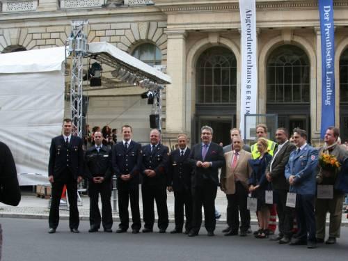 Gruppenfoto mit Ralf Wieland, vielen Männern und einer Ffrau vor dem Abgeordnetenhaus. Im Hintergrund sieht man auch noch eine Bühne. Einige Männer tragen Uniform.