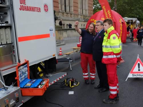 Veranstaltung auf der Straße vor dem Abgeordnetenhaus. Personen der Johanniter erklären Ralf Wieland etwas.