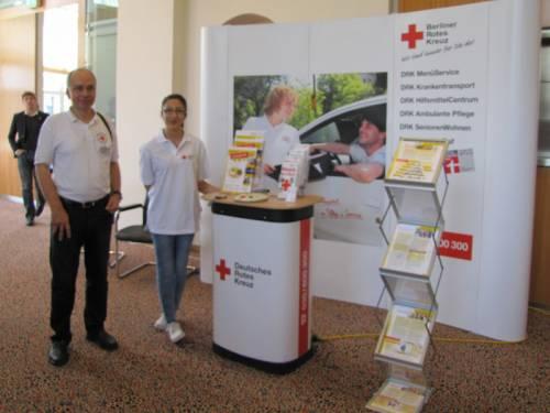 Messestand vom Deutschen Roten Kreuz im Abgeordnetenhaus. Ein Mann und eine Frau stehen lächelnd daneben.